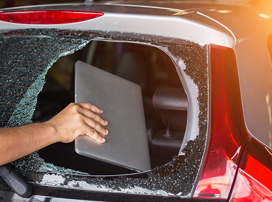 thief-stealing-a-laptop-from-a-car-through-a-broken-window